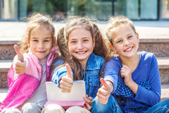 School students with tablet. Successful school students sitting with tablet in front of a school stock photos