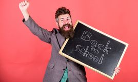 School and studying concept. Teacher welcomes students while holds chalkboard inscription back to school. Positive stock image