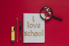 School stuff and magnifying glass with eyes looking at `I love school` lettering on a notebook. Red background. Back to school funny concept with wooden letters Royalty Free Stock Photo