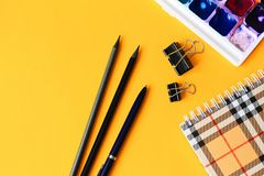 School subjects: pencils, notebook, watercolor paints on a light yellow background. Back to school concept stock photography