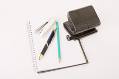 School Supplies. Notepad, pencil, pen, hole punch and stapler on white background royalty free stock image