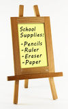 School supplies. List of back to school supplies in wooden frame on easel isolated on white background stock photography