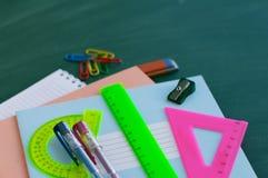 School supplies against a green board. Stock Photos