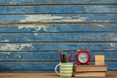 School supplies, alarm clock and wooden blocks on table Royalty Free Stock Photography