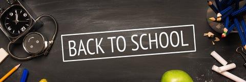 School supplies, alarm, pencils, apple on black chalkboard stock photo