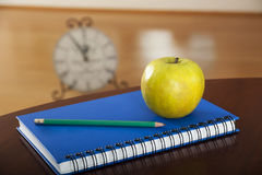School supplies with apple on wooden table Royalty Free Stock Photos