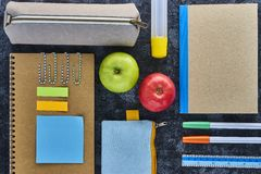 School supplies and apples on blackboard background. Top view with copy space Royalty Free Stock Photos