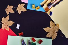 School supplies and autumn leaves on the brown background royalty free stock photo