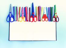 Back to School design elements. Colorful markers and scissors on opened empty notepad on light blue paper backgro. School supplies. Back to School design royalty free stock images