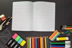 School supplies on black board background, with open notebook. Education, back to school concept with copy space