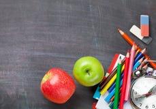 School supplies on blackboard background Royalty Free Stock Photos