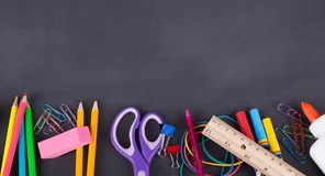 School Supplies on a Blackboard Background Royalty Free Stock Photo