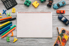 School supplies and blank notebook. Top view of blank notebook, school supplies and toys on a white wooden desk Royalty Free Stock Photos