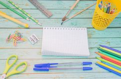 School supplies. Blue ballpens, color markers, pencils in a yellow stand, two tassels, ruler, yellow ruber, color clips stock photo