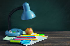 School supplies and blue desk lamp on a wooden surface against a blackboard. Stock Photography