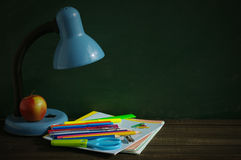 School supplies and blue desk lamp on a wooden surface against a blackboard. Royalty Free Stock Photos
