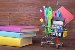School supplies with books. Shopping cart with school supplies with books on wooden table Royalty Free Stock Images