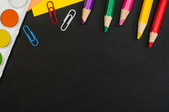 School supplies border on black chalkboard background. Top view photograph royalty free stock photos