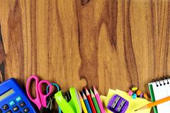 School supplies bottom border on wood desk background Stock Photography