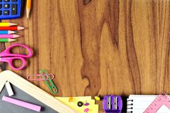 School supplies bottom corner border on wood desk background Royalty Free Stock Image