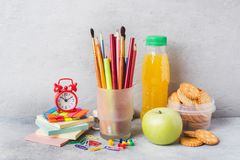 School supplies and Breakfast crackers, orange juice and fresh Apple on the grey table with copy space. concept school.  royalty free stock photos