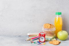 School supplies and Breakfast crackers, orange juice and fresh Apple on the grey table with copy space. concept school.  stock images
