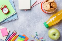 School supplies and Breakfast crackers, orange juice and fresh Apple on the grey table with copy space. concept school.  royalty free stock photo