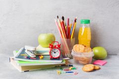 School supplies and Breakfast crackers, orange juice and fresh Apple on the grey table with copy space. concept school.  royalty free stock photography