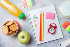 School supplies and Breakfast crackers, orange juice and fresh Apple on the grey table with copy space. concept school.  stock photo