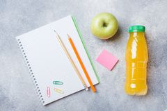 School supplies and Breakfast crackers, orange juice and fresh Apple on the grey table with copy space. concept school.  royalty free stock images