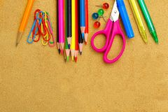 School supplies and bulletin board background. Colorful school supplies border on a bulletin board Royalty Free Stock Photo