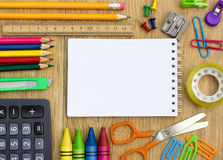 School supplies and checked notebook. On wood background Royalty Free Stock Image