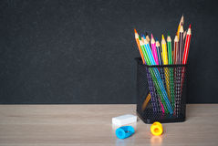 School  supplies on classroom table. In front of blackboard. View with copy space Royalty Free Stock Image