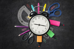 School supplies with a clock on the blackboard. High angle view of school supplies with an alarm clock on the blackboard Stock Photo
