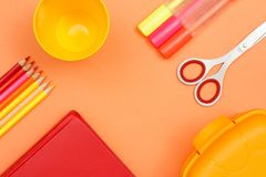 School supplies. Color pencils, book, plastic cup, felt pens, scissors and lunch box. On pink background. Top view with copy space. Back to school concept royalty free stock photo
