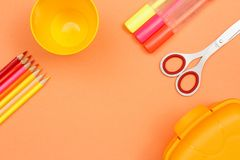 School supplies. Color pencils, plastic cup, felt pens, scissors and lunch box. On pink background. Top view with copy space. Back to school concept stock image