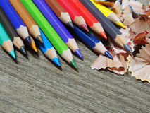 School supplies color pencils shavings on wooden board Stock Photography