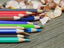 School supplies color pencils shavings on wooden board Stock Photo