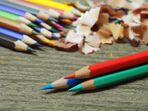 School supplies color pencils shavings on wooden board Royalty Free Stock Images