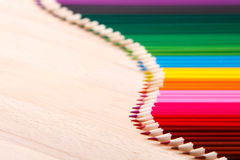 School supplies colored pencils forming a wave, on a wooden background Stock Photo