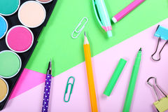 School supplies on colorful papers background Stock Photos