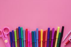 School supplies for Back To School concept. School supplies with coloured pen, scissors, and compasses on pink background for education concept royalty free stock photo