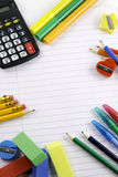 School supplies copy space. A group of school supplies set against a white notebook paper background Royalty Free Stock Photography