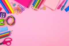 School supplies corner border over a pastel pink background Royalty Free Stock Photos
