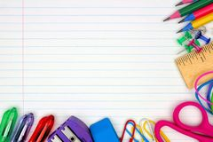 School supplies corner border on lined paper background. Colorful school supplies corner border over a lined paper background Stock Photo