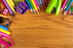 School supplies corner border on wood desk Royalty Free Stock Photos