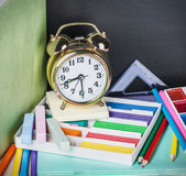 School supplies on the desk in the background of chalkboard Royalty Free Stock Images
