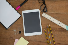 School supplies, digital tablet and spectacles on wooden table Royalty Free Stock Images
