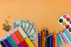 School supplies and dollars. Concept is to buy stationery objects. Top view Royalty Free Stock Photos