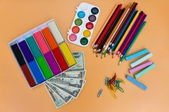 School supplies and dollars. Concept is to buy stationery objects. Top view Royalty Free Stock Photo